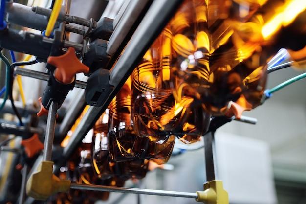 Промышленное производство пластиковых бутылок для слабоалкогольных напитков, газированной воды и подсолнечного масла. пустые пэт-бутылки коричневого цвета на фоне современного оборудования.