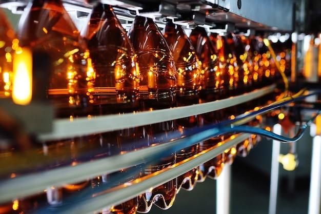 저 알코올 음료, 소다 및 해바라기 기름을위한 플라스틱 병의 산업 생산. 현대 장비의 배경에 갈색 색상의 빈 pet 병.