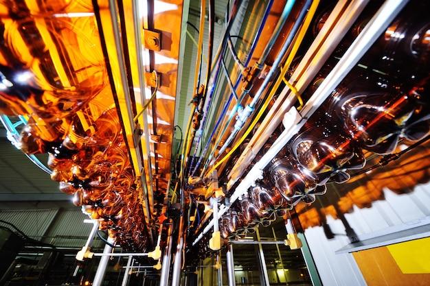 저알코올 음료, 소다 및 해바라기 기름을 위한 플라스틱 병의 산업 생산. 현대 장비의 배경에 갈색의 빈 pet 병.