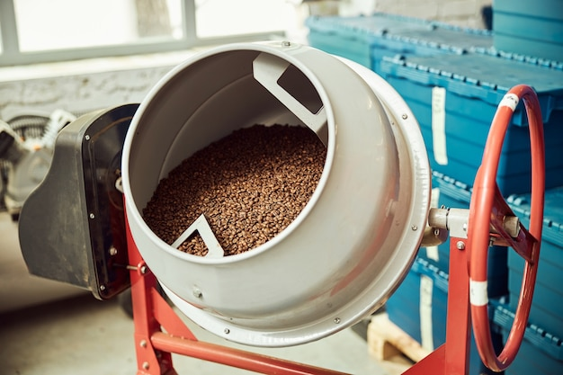 Industrial roaster machine with brown coffee beans or seeds of arabica coffee plant at factory