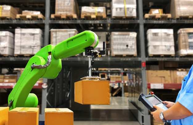 Industrial robot holding a box and worker operating a robot machine with a control panel on stock shelves background