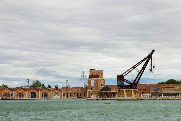 Промышленные верфи (arsenale di venezia) в италии, венеция. погрузочные краны и доки.
