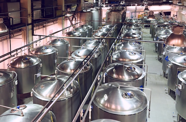 長い列に建てられた金属製のタンクがたくさんある工業店。現代の醸造生産。