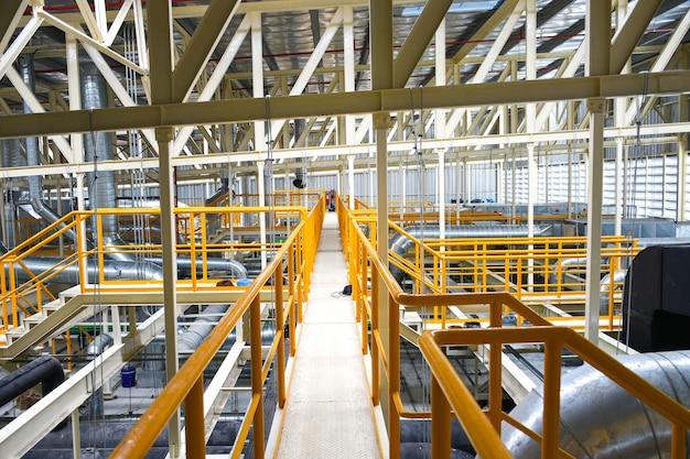 Промышленная дорожка с желтыми перилами и крышей стальной конструкции внутри фабрики