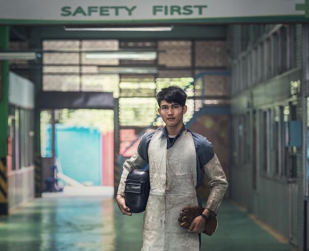 Industrial welder worker at factory workshop background