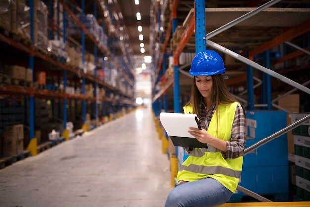 Industrial worker checking goods inventory in large warehouse storage center and writing report on distribution results