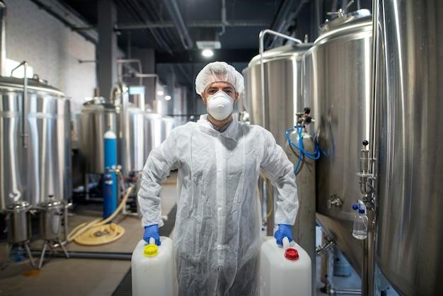 Промышленный рабочий держит пластиковые банки с химикатами на производственном предприятии