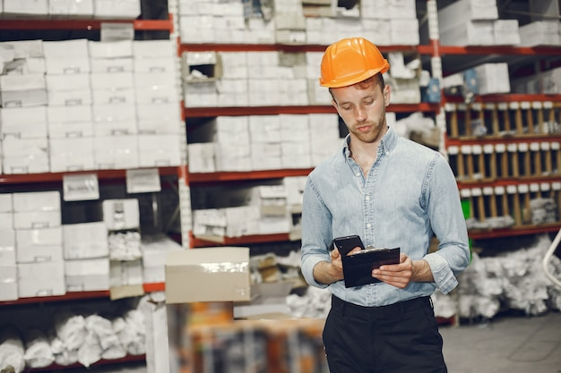 Industrial worker indoors in factory. businessman with orange hard hat. man in a blue shirt.