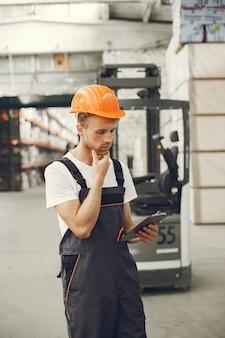 Operaio industriale al chiuso in fabbrica. giovane tecnico con elmetto arancione.