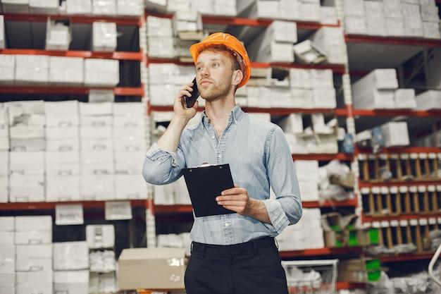 工場の屋内の産業労働者。オレンジ色のヘルメットを持つビジネスマン。青いシャツを着た男。