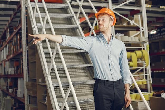 Промышленный рабочий в помещении на заводе. бизнесмен с оранжевой каской. мужчина в голубой рубашке.