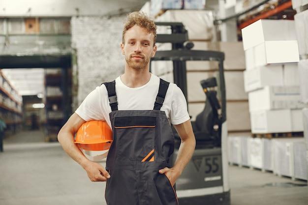 Промышленный рабочий в помещении на заводе. молодой техник в оранжевой каске.