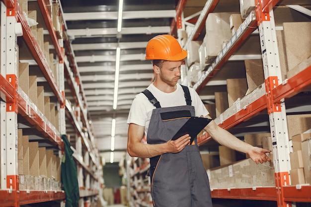 공장에서 실내 산업 노동자입니다. 오렌지 하드 모자와 젊은 기술자.