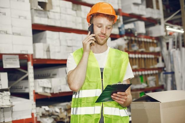 工場の屋内の産業労働者。オレンジ色のヘルメットをかぶった若い技術者。