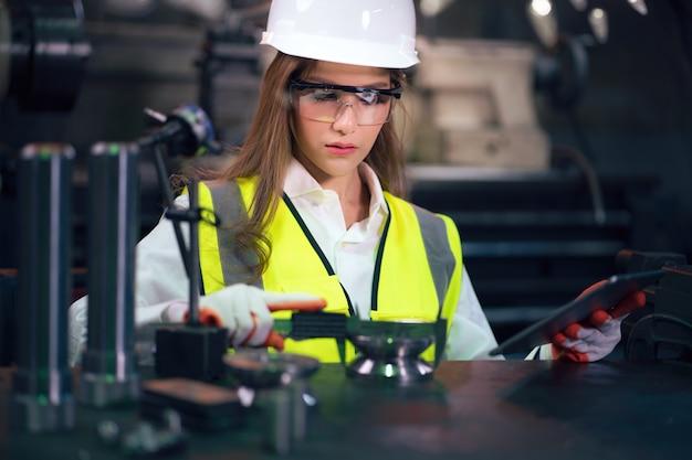 Инспектор промышленных рабочих, измеряющий детали с помощью штангенциркуля в заводской мастерской