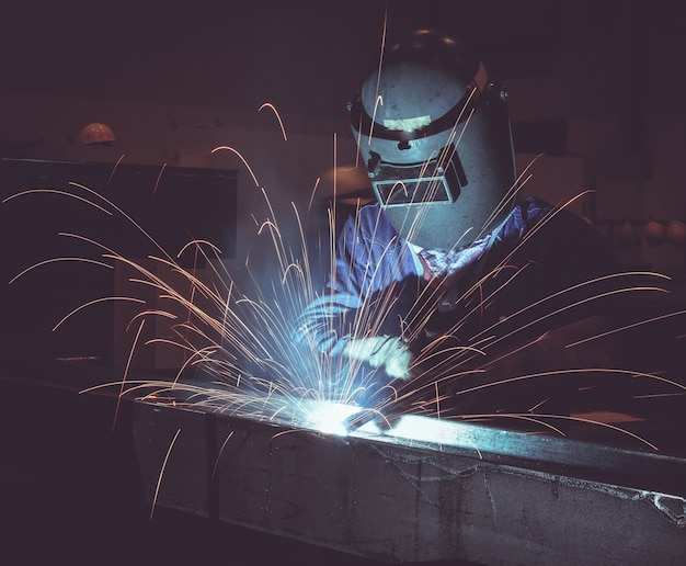 Industrial worker labourer at the factory welding steel structure