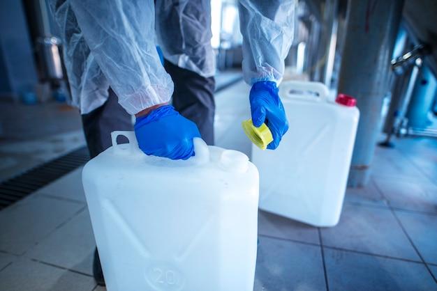 Промышленный рабочий открывает пластиковую канистру для использования химикатов.