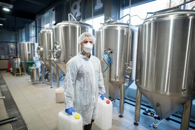 Промышленный рабочий-технолог в белом защитном костюме с сеткой для волос и маской держит пластиковые банки с химикатами на производственной линии пищевой фабрики