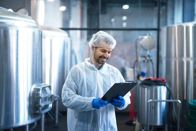 Промышленный рабочий-технолог в белом костюме с сеткой для волос и защитными перчатками смотрит на контрольный список и улыбается