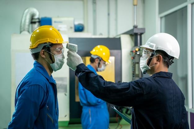 産業労働者は、工場で働く前に保護フェイスマスクのスキャン温度を着用します
