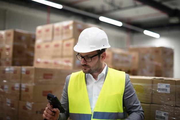 Operaio industriale con scanner di codici a barre che tiene traccia e controlla le merci in arrivo in magazzino