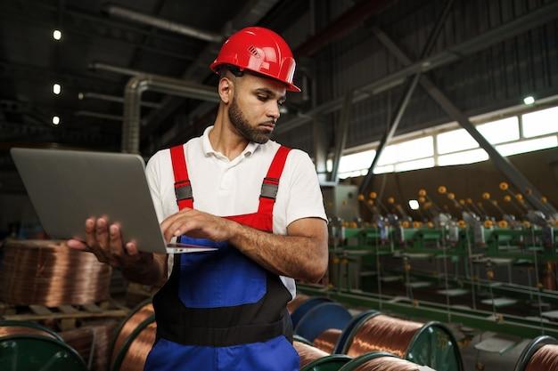 Промышленный рабочий с ноутбуком на заводе по производству кабеля