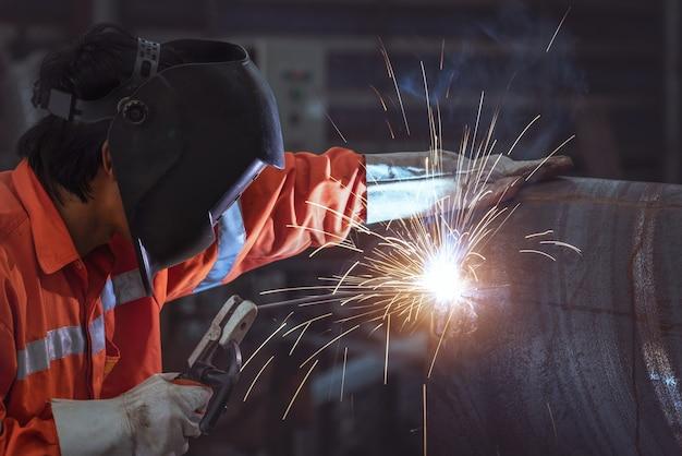 Промышленный рабочий с рабочим в защитной маске на заводе, сваривающем стальную трубу