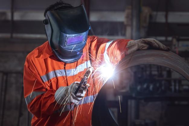 Промышленный рабочий с защитной маской, сваркой металлической трубы на заводе