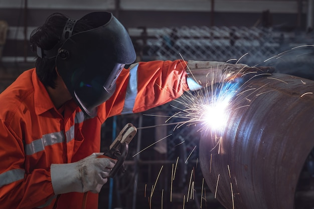 Промышленный рабочий с защитной маской, сваривающей стальную конструкцию на заводе