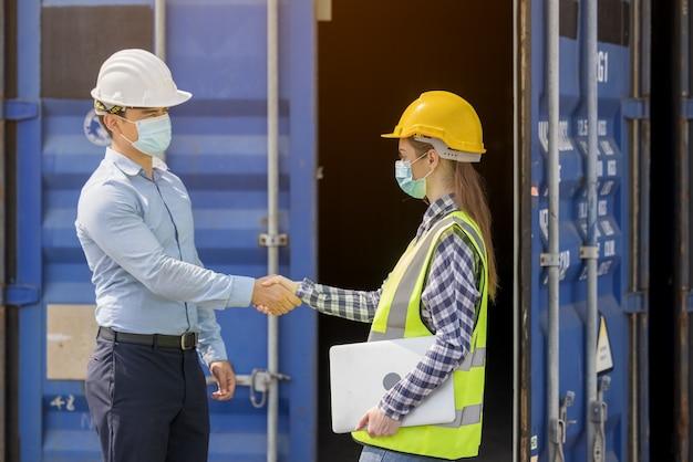 正面玄関でチェックしている産業労働者の女性とエンジニア制御労働者
