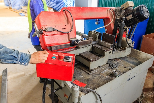 鉄鋼を切削して作業する労働者工場で赤色のマシン