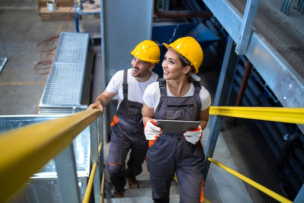 Промышленные рабочие-инженеры гуляют по фабрике и поднимаются по металлической лестнице