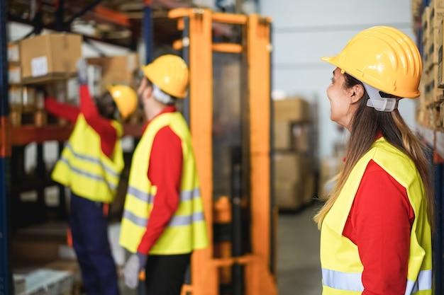 Промышленные рабочие, загружающие коробки для доставки внутри складского магазина - фокус на женской голове