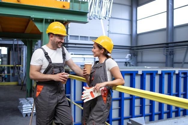 Lavoratori dell'industria in uniforme e attrezzature di sicurezza che si rilassano in una pausa bevendo caffè e parlando all'interno della fabbrica