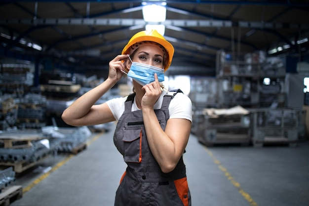 Industrial workman standing in factory hall and putting on hygienic mask on face to protect herself against highly contagious corona virus