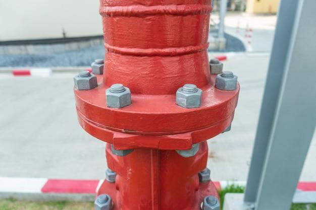 ボルトとナット付きの工業地帯の赤い鋼パイプライン