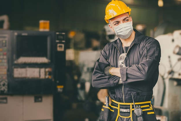 Промышленный инженер мужчина мужчина рабочий носить лицевую маску во время службы, работая на заводе, чтобы предотвратить загрязнение воздуха пылью вируса covid и для хорошего здоровья.