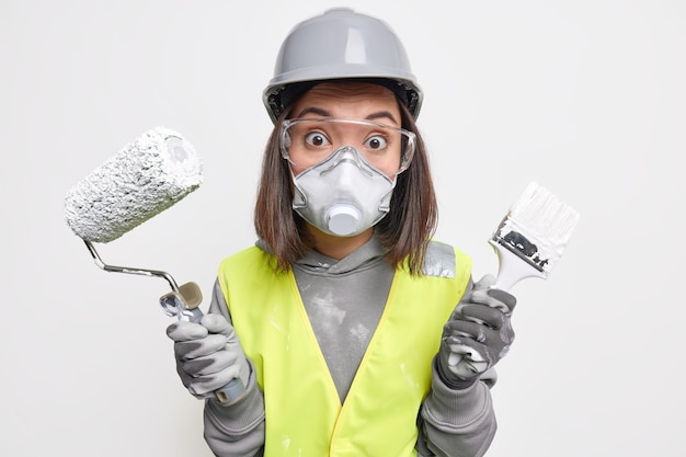 Industry engineering and consturction concept. surprised professional female engineer wears building uniform protective helmet glasses mask and gloves uses paint roller brush for redecoration