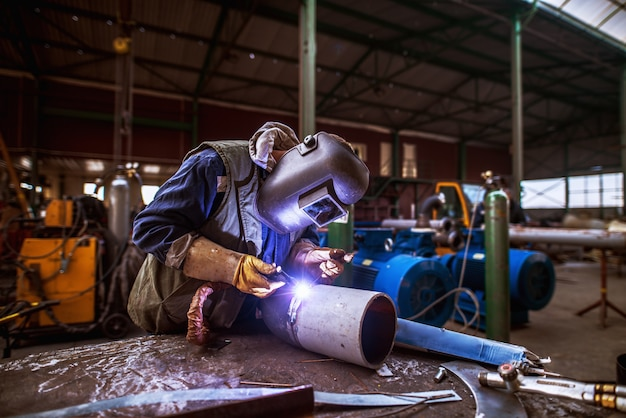 Industry male worker in protective uniform repairing metal pipe.