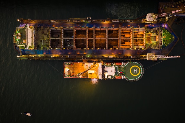 Industry shipyard and repairing large ships in the sea aerial view at night