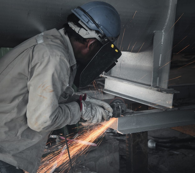 Industry worker cutting steel part manufacture workshop in factory