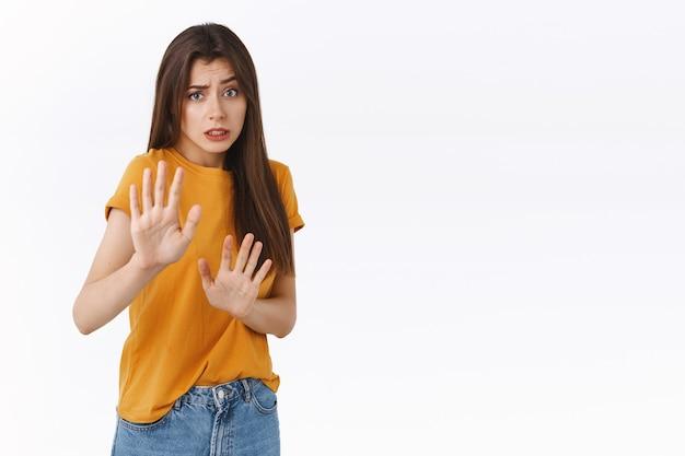 Inescura, riluttante, timida donna innocente spaventata in maglietta gialla, chiedendo di fermarsi o fare un passo indietro, facendo una smorfia dispiaciuta, rifiutando qualcosa con un'espressione imbarazzante e preoccupata, tirando le mani in segno di divieto