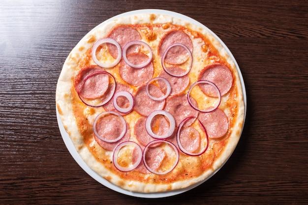 Недорогая пицца, с пепперони, луком, с томатным соусом. для любых целей.