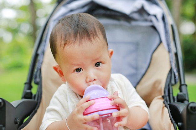 Infant baby boy on stroller and drinking water from baby sippy cup with straw