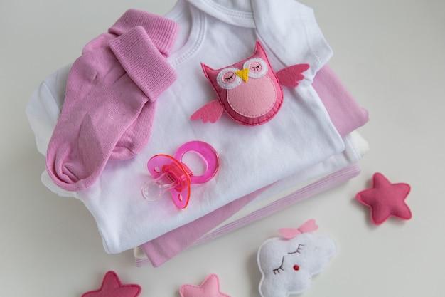 Младенческая детская одежда девочка соску колпачок на фоне