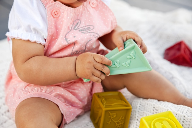 Infant baby girl sitting and playing with colorful rubber blocks on white blanket in the backyard during quarantine