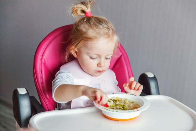Infant baby girl with dirty face eating soup herself with spoon in high baby chair in kitchen at home