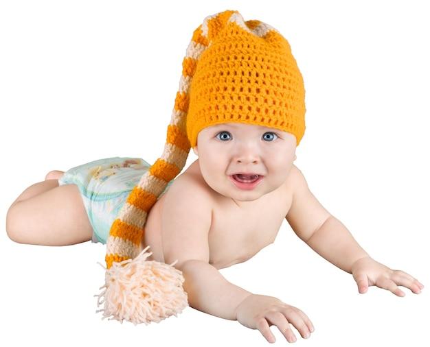 Младенец лежит на животе в вязаной детской шапочке