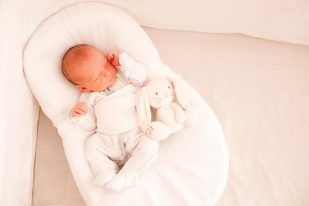 ベッドでパジャマを着て繭で眠っている幼児の赤ちゃん