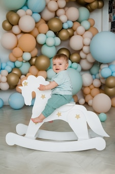 乳児育児の赤ちゃん男の子子供幼児座って乗る白い小さな木の馬のおもちゃ。風船の写真ゾーン。